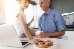 Ο ηληκιωμένος και το αγόρι πίνουν το τσάι στην κουζίνα Το αγόρι σύρεται στο κέικ Στοκ εικόνες με δικαίωμα ελεύθερης χρήσης