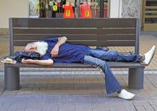 Ο ηληκιωμένος κοιμάται σε έναν πάγκο υπαίθριο στη Sofia, Βουλγαρία Στοκ Φωτογραφίες