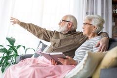 Ο ηληκιωμένος παρουσιάζει κάτι στη σύζυγο με τον ενθουσιασμό Στοκ Φωτογραφίες