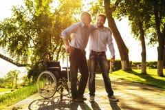 Ο ηληκιωμένος προσπαθεί να πάρει από την αναπηρική καρέκλα στα δεκανίκια Ο γιος του τον βοηθά Στοκ Εικόνα