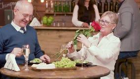 Ο ηληκιωμένος προσφέρει τα λουλούδια στην ημερομηνία του σε ένα ρομαντικό γεύμα φιλμ μικρού μήκους