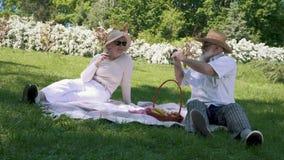 Ο ηληκιωμένος στο καπέλο φωτογραφίζει τη σύζυγο κομψότητάς του με το ποτήρι του κρασιού κατά τη διάρκεια του πικ-νίκ απόθεμα βίντεο