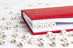 Ο ηττημένος λέξης που γράφεται στους ξύλινους φραγμούς στο κόκκινο σημειωματάριο στο λευκό επιζητά στοκ φωτογραφίες