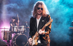 Ο ηλεκτρικός κιθαρίστας με το βράχο - και - κυλά τη ζώνη εκτελώντας τη μουσική σκληρής ροκ στοκ εικόνες