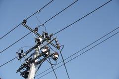 Ο ηλεκτρικός πόλος συνδέει με τα ηλεκτρικά καλώδια υψηλής τάσης στο μπλε ουρανό Στοκ Φωτογραφία