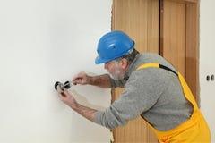 Ο ηλεκτρολόγος στο εργοτάξιο οικοδομής εγκαθιστά το ηλεκτρικό βούλωμα Στοκ Εικόνες