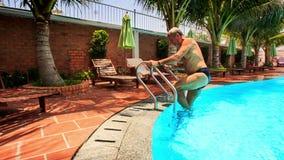 Ο ηληκιωμένος βγαίνει από την πισίνα κάθεται στο δίπλωμα της έδρας απόθεμα βίντεο