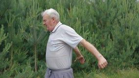 Ο ηληκιωμένος κάνει τα δάχτυλα χεριών τεντωμάτων ασκήσεων πρωινού στο πάρκο με τα κωνοφόρα απόθεμα βίντεο