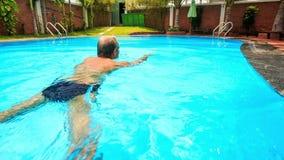 Ο ηληκιωμένος πίσω πλευρών κινηματογραφήσεων σε πρώτο πλάνο κολυμπά στο κυανό νερό λιμνών φιλμ μικρού μήκους