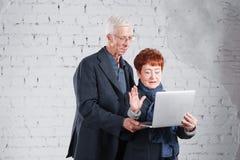 Ο ηλικιωμένος άνθρωπος κρατά ένα lap-top και επικοινωνεί μέσω του Διαδικτύου Ευτυχής μόνιμη αγκαλιά ζευγών grandma grandpa χαμόγε Στοκ εικόνα με δικαίωμα ελεύθερης χρήσης