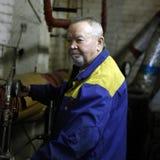 Ο ηλικιωμένος μηχανικός ατόμων ρυθμίζει τον εξοπλισμό Στοκ Εικόνες