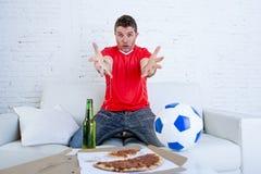 Ο θαυμαστής ποδοσφαίρου στο ποδοσφαιρικό παιχνίδι προσοχής του Τζέρσεϋ ομάδων στη TV ξαπλώνει στο σπίτι που απογοητεύεται Στοκ φωτογραφία με δικαίωμα ελεύθερης χρήσης