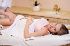 Ο θεράπων μασάζ κάνει ένα μασάζ ποδιών για μια έγκυο γυναίκα Στοκ Εικόνες
