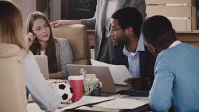 Ο θετικός αρσενικός αρχηγός ομάδας αφροαμερικάνων γελά στη multiethnic συζήτηση επιχειρησιακής συνεδρίασης ομάδων γραφείων σε αργ απόθεμα βίντεο