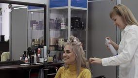 Ο θετικός κομμωτής γυναικών κάνει ένα ογκώδες όμορφο Hairstyle φιλμ μικρού μήκους