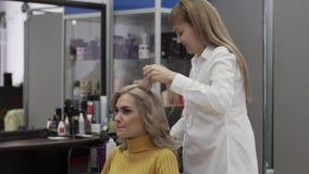 Ο θετικός κομμωτής γυναικών κάνει ένα ογκώδες όμορφο Hairstyle απόθεμα βίντεο