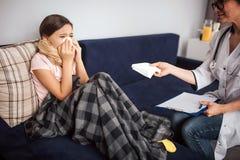 Ο θετικός νέος γιατρός κάθεται στον καναπέ του παιδιού Δίνει τον ιστό στο κορίτσι Αυτή που φτερνίζεται Τα πόδια της που καλύπτοντ στοκ εικόνα με δικαίωμα ελεύθερης χρήσης