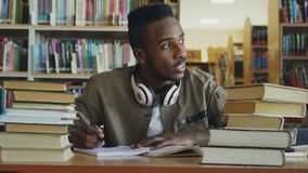 Ο θετικός νέος όμορφος τύπος αφροαμερικάνων με τα μεγάλα ακουστικά κάθεται στον πίνακα με τα βιβλία, κοιτάζοντας μέσω του παραθύρ απόθεμα βίντεο