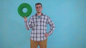 Ο θετικός νεαρός άνδρας στα γυαλιά σε ένα μπλε υπόβαθρο και κρατά ένα πράσινο ορθοπεδικό μαξιλάρι από τα hemorrhoids απόθεμα βίντεο
