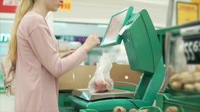 Ο θηλυκός αγοραστής ζυγίζει τα λαχανικά σε μια κλίμακα σε μια υπεραγορά απόθεμα βίντεο