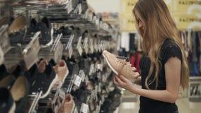 Ο θηλυκός αγοραστής θεωρεί τα παπούτσια σε ένα κατάστημα, κρατώντας ένα ζευγάρι στα χέρια φιλμ μικρού μήκους