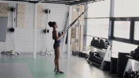 Ο θηλυκός αθλητής εκπαιδεύει με τους βρόχους trx στην αθλητική λέσχη απόθεμα βίντεο