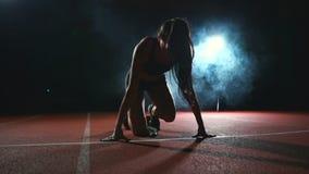 Ο θηλυκός αθλητής σε ένα σκοτεινό υπόβαθρο προετοιμάζεται να τρέξει την ανώμαλη ορμή από τα μαξιλάρια treadmill στο α απόθεμα βίντεο