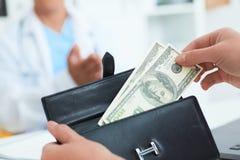 Ο θηλυκός ασθενής παίρνει από το πορτοφόλι της τους λογαριασμούς εκατό δολαρίων για να πληρώσει για τις υπηρεσίες ενός γιατρού Δω Στοκ φωτογραφία με δικαίωμα ελεύθερης χρήσης
