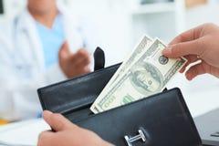 Ο θηλυκός ασθενής παίρνει από το πορτοφόλι της τους λογαριασμούς εκατό δολαρίων για να πληρώσει για τις υπηρεσίες ενός γιατρού Δω Στοκ φωτογραφίες με δικαίωμα ελεύθερης χρήσης