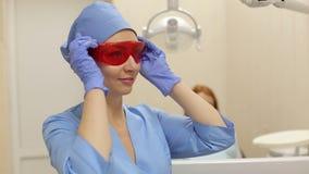 Ο θηλυκός γιατρός βάζει στα πορτοκαλιά προστατευτικά δίοπτρα πέρα από τα μάτια της πρίν συνεργάζεται με έναν πελάτη φιλμ μικρού μήκους