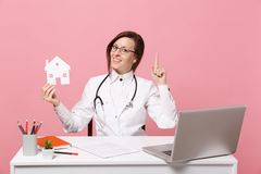 Ο θηλυκός γιατρός κάθεται στην εργασία γραφείων για τον υπολογιστή με το ιατρικό σπίτι λαβής εγγράφων στο νοσοκομείο που απομονών στοκ φωτογραφία με δικαίωμα ελεύθερης χρήσης