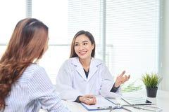 Ο θηλυκός γιατρός μιλά στο θηλυκό ασθενή στο γραφείο νοσοκομείων γράφοντας στο αρχείο υγείας ασθενών στον πίνακα Υγειονομική περί στοκ φωτογραφίες με δικαίωμα ελεύθερης χρήσης