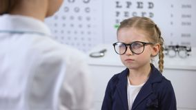 Ο θηλυκός γιατρός που βάζει τα γυαλιά στο δυσαρεστημένο κορίτσι, παιδί αισθάνεται επισφαλής, ανατρεμμένος απόθεμα βίντεο