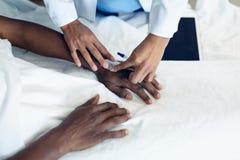 Ο θηλυκός γιατρός που συνδέει IV σταλαγματιά στον αρσενικό ασθενή παραδίδει το θάλαμο στοκ εικόνες
