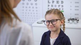 Ο θηλυκός γιατρός που φορά τα γυαλιά στο ευτυχές παιδί, διαμορφώνει eyewear στο οπτικό κατάστημα απόθεμα βίντεο
