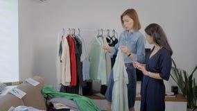 Ο θηλυκός εικόνα-κατασκευαστής συμβουλεύεται μια νέα γυναίκα brunette στο δωμάτιο επίπεδου, συζητώντας τα πουκάμισα και ντύνει απόθεμα βίντεο