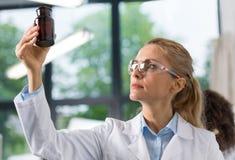 Ο θηλυκός επιστήμονας εξετάζει το μπουκάλι με τις χημικές ουσίες που λειτουργούν στο σύγχρονο εργαστήριο, ελκυστικός ερευνητής γυ στοκ φωτογραφίες με δικαίωμα ελεύθερης χρήσης