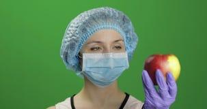 Ο θηλυκός επιστήμονας επιλέγει τη σύριγγα με τα φάρμακα ή ένα μήλο απόθεμα βίντεο