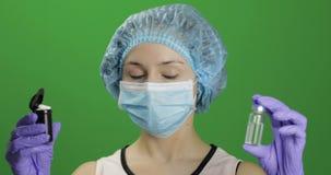 Ο θηλυκός επιστήμονας επιλέγει το φιαλλίδιο του εμβολιασμού ή του πλαστικού βάζου με τα χάπια απόθεμα βίντεο