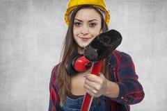 Ο θηλυκός εργάτης οικοδομών παρουσιάζει μεγάλο σφυρί Στοκ Εικόνες