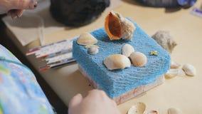 Ο θηλυκός καλλιτέχνης κάνει ένα σχέδιο στο μπλε κιβώτιο εγγράφου τοπ κάλυψης με τα κοχύλια θάλασσας απόθεμα βίντεο