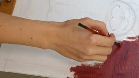 Ο θηλυκός καλλιτέχνης χρωματίζει το έργο τέχνης εικόνων στο στούντιο τέχνης φιλμ μικρού μήκους