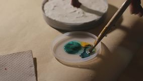 Ο θηλυκός καλλιτέχνης χρωματίζει το χειροποίητο δέντρο καλωδίων πριν από τη διαδικασία βερνικιών φιλμ μικρού μήκους