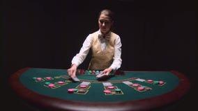 Ο θηλυκός κρουπιέρης χαρτοπαικτικών λεσχών διανέμει γιατί το επιτραπέζιο πόκερ τρία κάρτες είναι η πτώση Μαύρη ανασκόπηση κίνηση  φιλμ μικρού μήκους