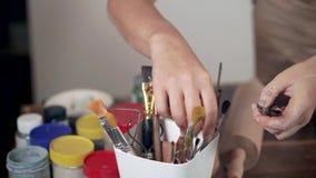 Ο θηλυκός κύριος επιλέγει τα εργαλεία για τη διαμόρφωση αργίλου, κινημ φιλμ μικρού μήκους