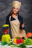 Ο θηλυκός μάγειρας αρχιμαγείρων κρατά το μπουκάλι με το πετρέλαιο Στοκ Εικόνες