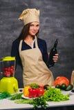 Ο θηλυκός μάγειρας αρχιμαγείρων κρατά το μπουκάλι με το πετρέλαιο Στοκ φωτογραφία με δικαίωμα ελεύθερης χρήσης
