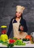 Ο θηλυκός μάγειρας αρχιμαγείρων κρατά το μπουκάλι με το πετρέλαιο Στοκ εικόνες με δικαίωμα ελεύθερης χρήσης