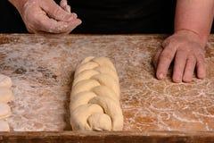 Ο θηλυκός μάγειρας θα ψεκάσει με τη ζύμη παπαρουνών που υφαίνεται σε μια πλεξίδα Στοκ Εικόνες