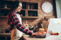 Ο θηλυκός μάγειρας στην ποδιά εξετάζει μια συνταγή στο lap-top Στοκ Εικόνα